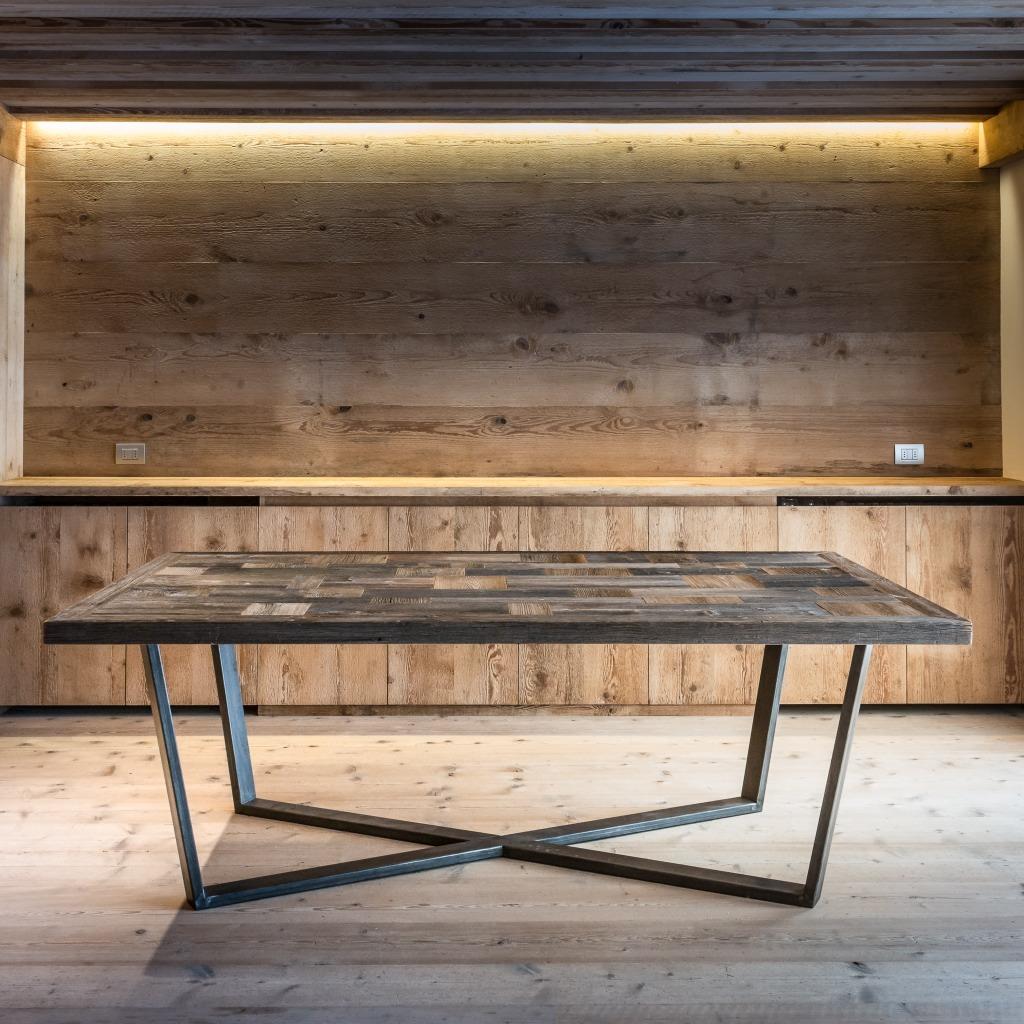 <p>Questo tavolo dalle linee geometriche ha un piano a forme, costituito da rettangoli in legno pregiato e gambe di ferro. Il Design riprende le linee del più maestoso massiccio delle zona ampezzana: le Tofane. La sfumatura grigia è data dall'esposizione agli agenti atmosferici del legno che ricopriva l'esterno dei fienili. La parola Pestuze, in dialetto […]</p>